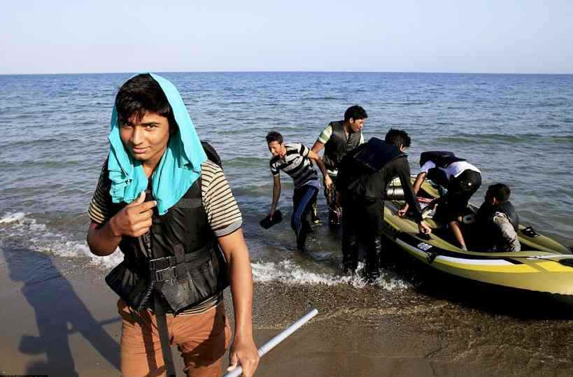 KOS2B326BBD00000578-3190377-New_arrivals_An_Afghan_migrant_smiles_as_he_reaches_the_sands_of-a-56_1439044784087