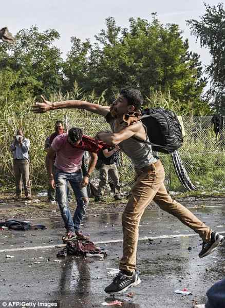 ungheria2C62594800000578-3236418-A_refugee_throws_a_stone_towards_Hungarian_riot_police_after_the-m-26_1442424117788