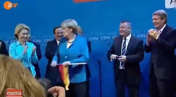 Merkel rifiuta bandiera tedesca con aria schifata – VIDEO