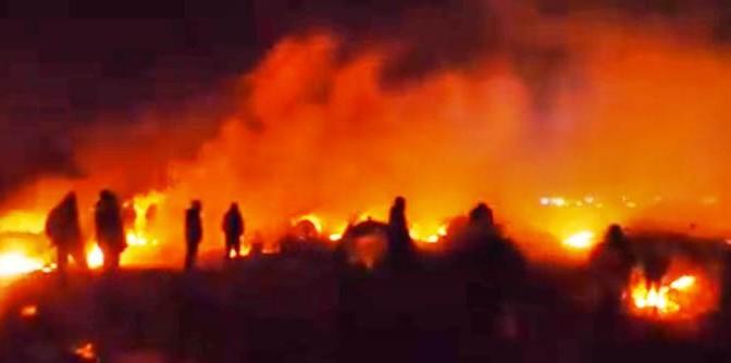 APOCALISSE DI FUOCO A CALAIS: PROFUGHI DEVASTANO CAMPO, ASSALTANO POLIZIA – VIDEO