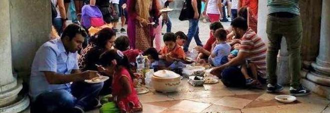 Famiglia di migranti prepara il pranzo in piazza San Marco