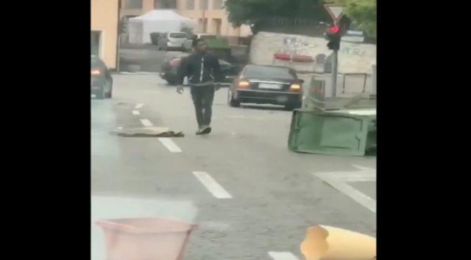 Migrante sfascia tutto: rovescia cassonetti e attacca i passanti, le auto – VIDEO