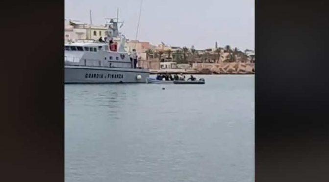 Scafismo di Stato, motovedetta traina barcone carico di invasori – VIDEO